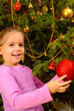 Adorable toddler girl holding decorative Christmas toy ball Royalty Free Stock Photo