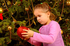 Adorable toddler girl holding decorative Christmas toy ball Stock Images