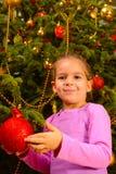 Adorable toddler girl holding decorative Christmas toy ball Stock Photo