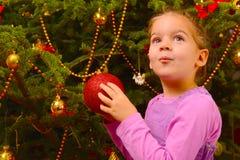 Adorable toddler girl holding decorative Christmas toy ball Stock Photos