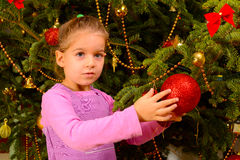 Adorable toddler girl holding decorative Christmas toy ball Royalty Free Stock Image
