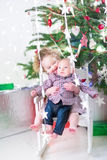 Adorable toddler girl holding her baby brother under Christmas tree Royalty Free Stock Image