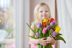 Adorable toddler girl holding tulips by the window Stock Images