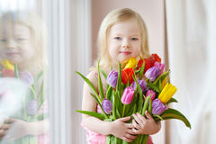 Adorable toddler girl holding tulips by the window Stock Photography