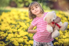Adorable toddler girl holding white teddy bear. Adorable little toddler girl with a white teddy bear having fun in summer park on beautiful sunny day with yellow royalty free stock image