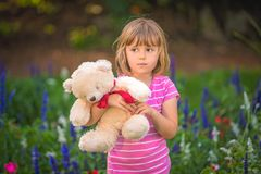 Adorable toddler girl holding white teddy bear. Adorable little toddler girl with a white teddy bear having fun in summer park on beautiful sunny day with yellow stock photo