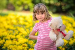 Adorable toddler girl holding white teddy bear. Adorable little toddler girl with a white teddy bear having fun in summer park on beautiful sunny day with yellow stock photography