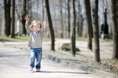 Adorable toddler girl jumping outdoors Stock Photos