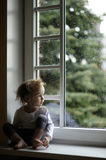 Adorable toddler girl looking at raindrops Royalty Free Stock Images
