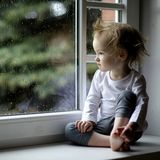 Adorable toddler girl looking at raindrops Royalty Free Stock Photos