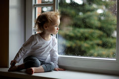 Adorable toddler girl looking though the window Stock Photo