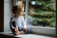 Adorable toddler girl looking though the window. Adorable toddler girl looking at raindrops on the window Royalty Free Stock Images
