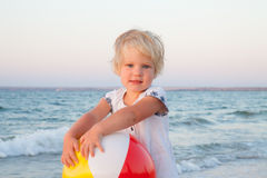 Adorable toddler girl playing with ball on sand beach Stock Images