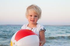 Adorable toddler girl playing ball on sand beach Royalty Free Stock Photos