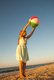 Adorable toddler girl playing ball on sand beach Stock Images