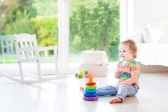 Adorable toddler girl playing in beautiful white room stock photography