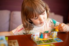 Adorable toddler girl playing board game indoors