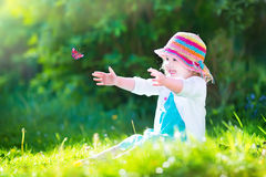 Adorable toddler girl playing with butterfly Stock Photo
