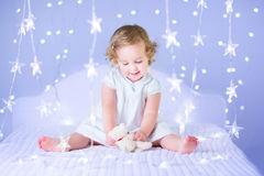 Adorable toddler girl playing with her toy bear between soft lights in star shape Royalty Free Stock Photo