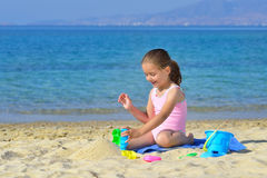 Adorable toddler girl playing with her toys at the beach Royalty Free Stock Images