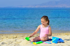 Adorable toddler girl playing with her toys at the beach Royalty Free Stock Image