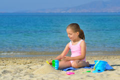 Adorable toddler girl playing with her toys at the beach Royalty Free Stock Photos