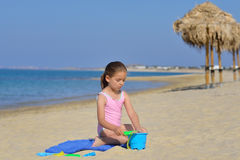 Adorable toddler girl playing with her toys at the beach Stock Image