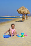 Adorable toddler girl playing with her toys at the beach Stock Photography