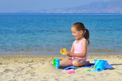 Adorable toddler girl playing with her toys at the beach Royalty Free Stock Photo
