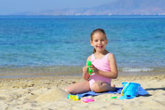 Adorable toddler girl playing with her toys at the beach Stock Photo