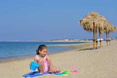 Adorable toddler girl playing with her toys at the beach Royalty Free Stock Photography