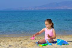 Adorable toddler girl playing with her toys at beach Stock Images