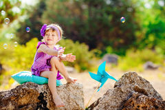 Adorable toddler girl playing outdoors in green summer park Royalty Free Stock Images