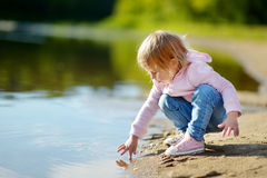 Adorable toddler girl playing by a river Stock Images