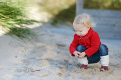 Adorable toddler girl playing in a sand Royalty Free Stock Photography