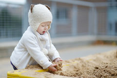 Adorable toddler girl playing in a sandbox Royalty Free Stock Photography