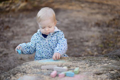 Adorable toddler girl playing with sidewalk chalk Royalty Free Stock Photography