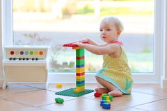 Adorable toddler girl playing with toys on the floor Stock Photo