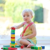 Adorable toddler girl playing with toys on the floor Royalty Free Stock Photos