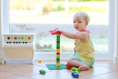 Adorable toddler girl playing with toys on the floor Royalty Free Stock Photo
