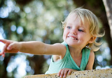Adorable toddler girl pointing with finger,  shallow focuse Royalty Free Stock Photography
