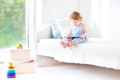 Adorable toddler girl reading a book sitting on bed Royalty Free Stock Photo