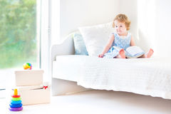 Adorable toddler girl reading book sitting on white bed royalty free stock photo