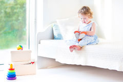 Adorable toddler girl reading book sitting on white bed Stock Photography