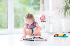 Adorable toddler girl reading book in sunny room stock image
