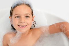Adorable toddler girl relaxing in bathtub Stock Image