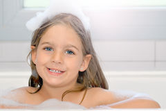 Adorable toddler girl relaxing in bathtub Stock Photos