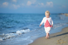 Adorable toddler girl on a sandy beach Stock Images