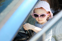 Adorable toddler girl sitting in a car Stock Images