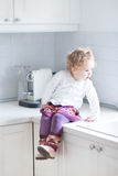 Adorable toddler girl sitting in kitchen on countert Royalty Free Stock Image